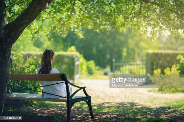a woman relaxing in a green garden - sitting foto e immagini stock
