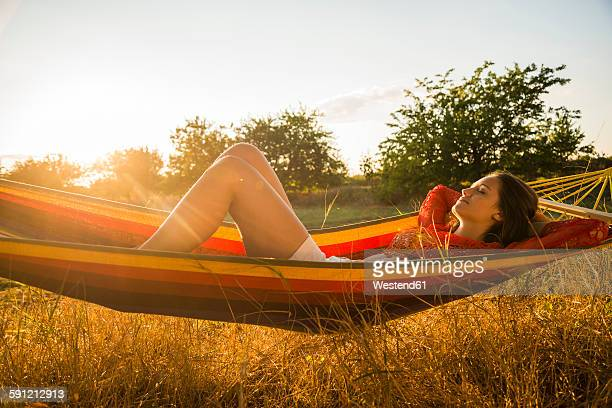 Woman relaxing in a hammock at backlight