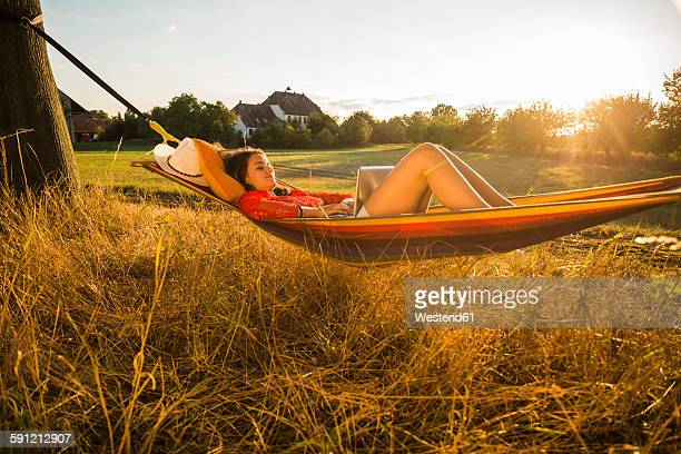 Woman relaxing in a hammock while using laptop