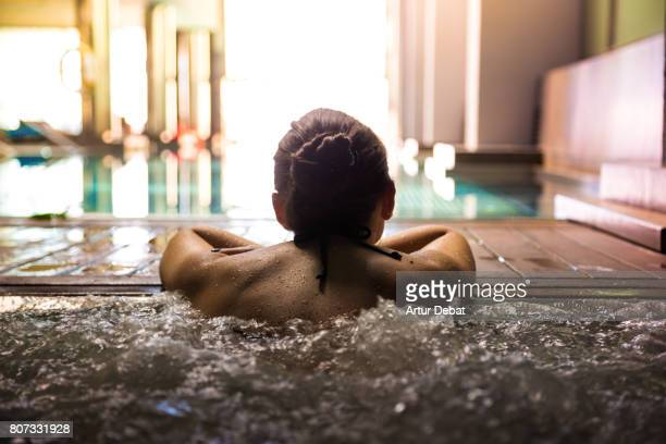 woman relaxing in a hot tub pool during weekend days of relax and spa in a luxury place during travel vacations. - sauna und nassmassage stock-fotos und bilder