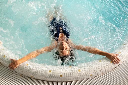 Woman Relaxing in a Hydro Massage Pool - gettyimageskorea