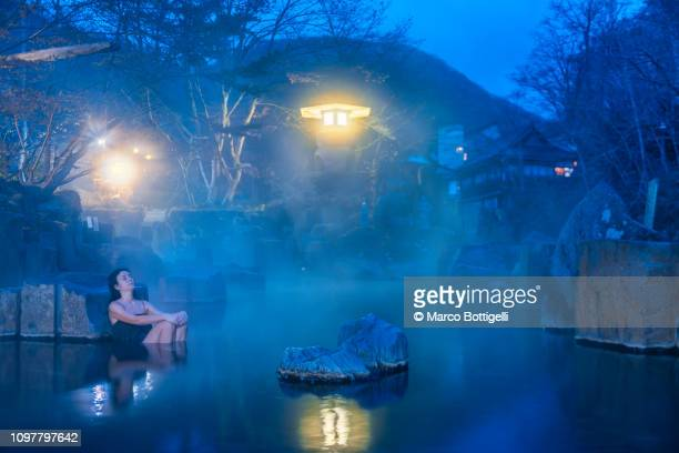 woman relaxing in a japanese hot spring at dawn. - hot spring stock pictures, royalty-free photos & images