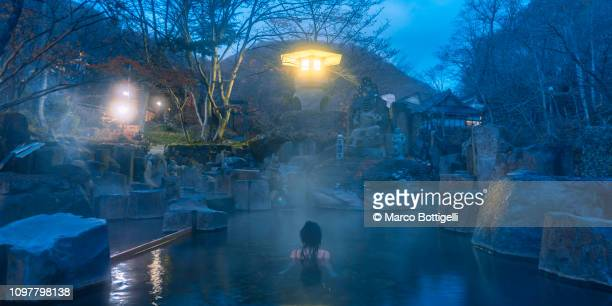 woman relaxing in a japanese hot spring at dawn. - 温泉 ストックフォトと画像