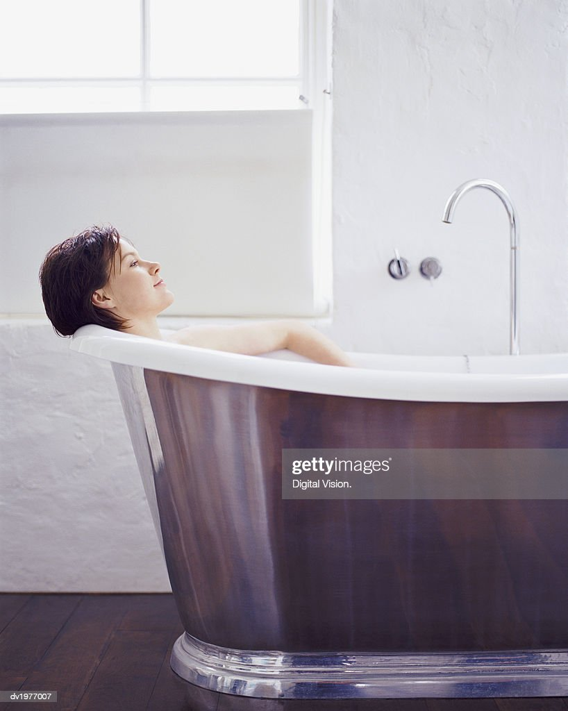 Woman Relaxing in a Modern Metallic Bath : Stock Photo