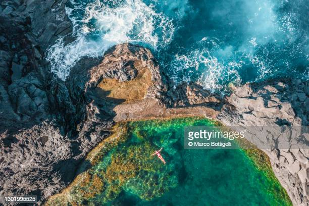 woman relaxing in a natural pool - tourist stock pictures, royalty-free photos & images