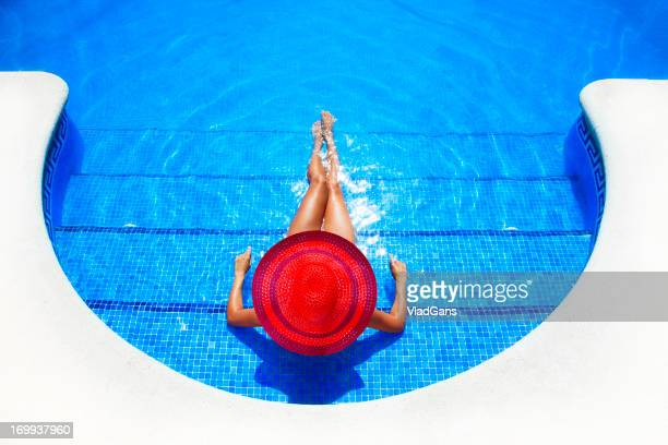 woman relaxing in a resort swimming pool - red hat stock pictures, royalty-free photos & images