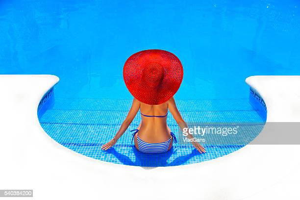 woman relaxing in a resort swimming pool - sun hat stock pictures, royalty-free photos & images