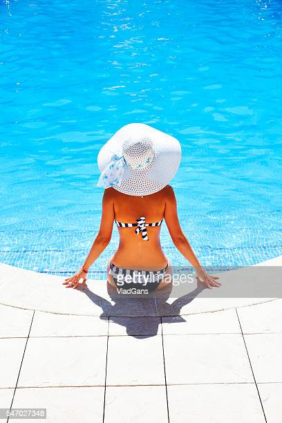 Femme se détendre dans la piscine du centre de villégiature