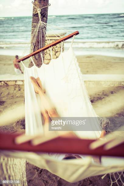 Woman relaxing in a white hammock by the beach