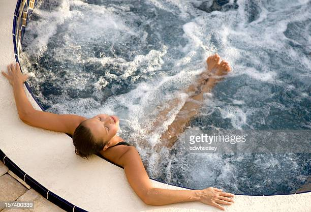 woman relaxing in an outdoor hot tub - hot tub stock photos and pictures