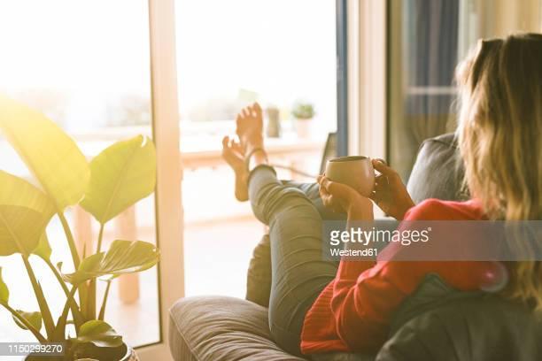 woman relaxing in armchair at home holding coffee cup - gemak stockfoto's en -beelden