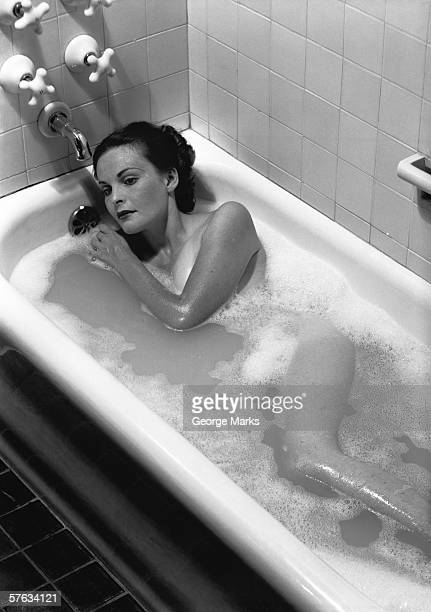 Woman relaxing in bath, (B&W), elevated view
