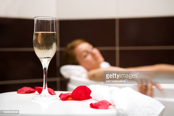 Woman relaxing in bath with glass of wine and rose petals