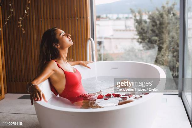 woman relaxing in bathtub at bathroom - red tub photos et images de collection