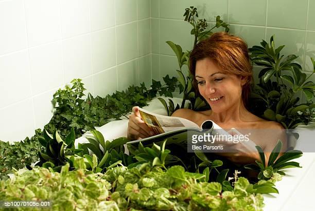 Femme se détendre dans la baignoire avec ses plantes, lisant un magazine
