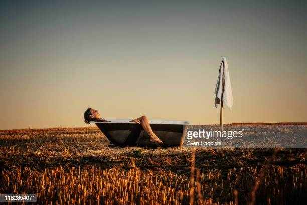 woman relaxing in bathtub in rural field - simple living stock pictures, royalty-free photos & images
