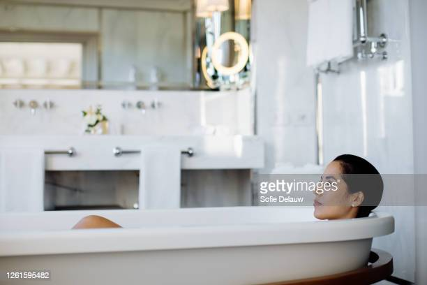 woman relaxing in bathtub in suite - florence douillet photos et images de collection
