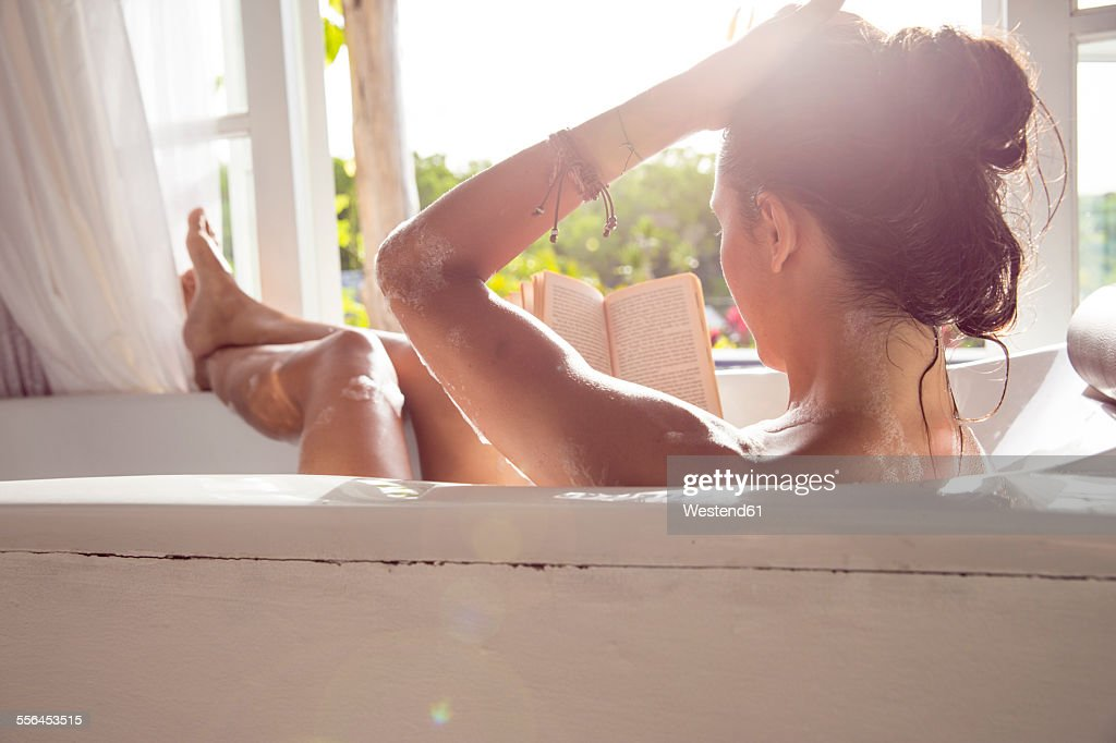Woman relaxing in bathtub reading book : Stock Photo