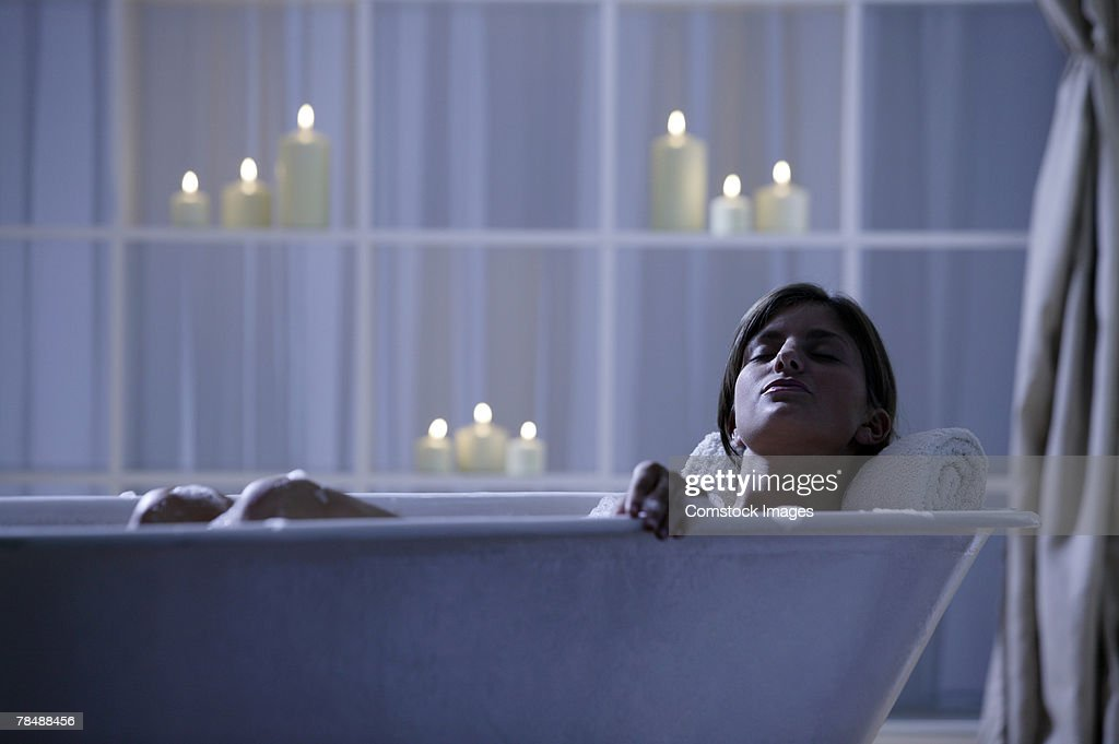 Woman relaxing in bathtub with lit candles : Stock Photo