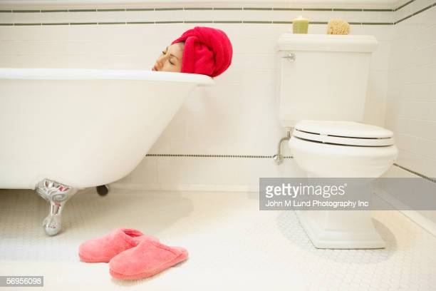 Woman relaxing in bathtub with towel wrapped around head