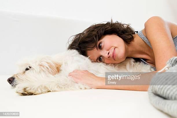 Frau entspannenden im Bett mit Hund