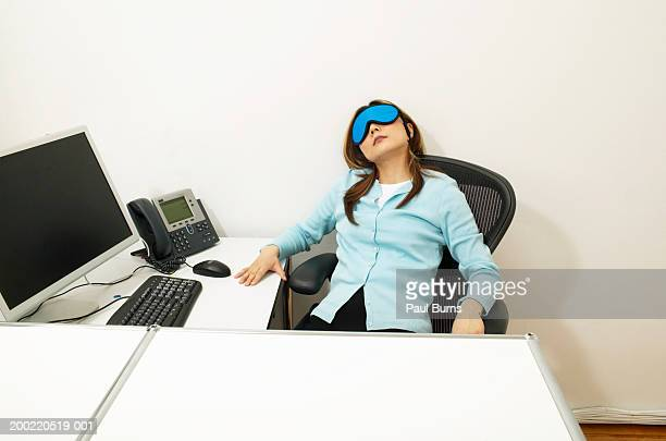 Woman relaxing in chair at desk wearing eye mask