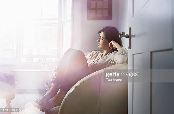 woman relaxing in chair in house