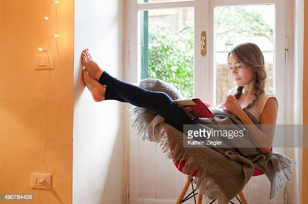 woman relaxing in chair, reading on digital tablet - レギンス ストックフォトと画像