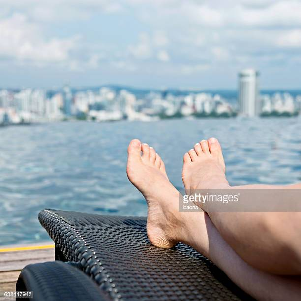 Woman relaxing in city infinity pool