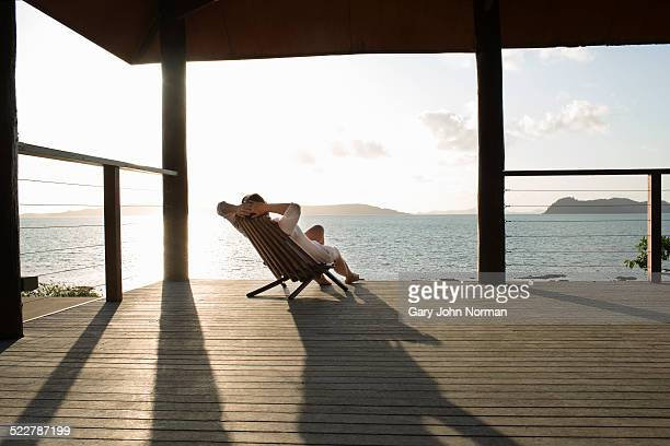 woman relaxing in deck chair on veranda. - beauty in nature stock pictures, royalty-free photos & images