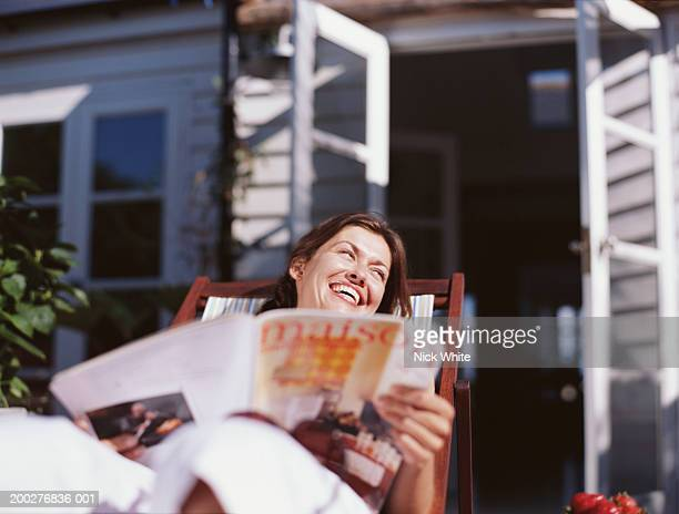 woman relaxing in deckchair holding magazine, leaning back laughing - magazine stock pictures, royalty-free photos & images