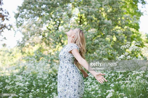 woman relaxing in field of flowers - dress stock pictures, royalty-free photos & images
