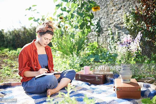 Woman relaxing in garden with note pad and pencil.