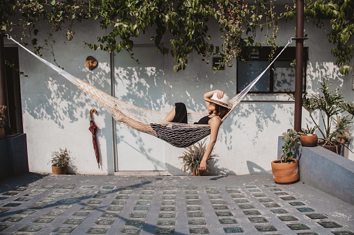 Woman Relaxing In Hammock Against Wall At Yard - gettyimageskorea