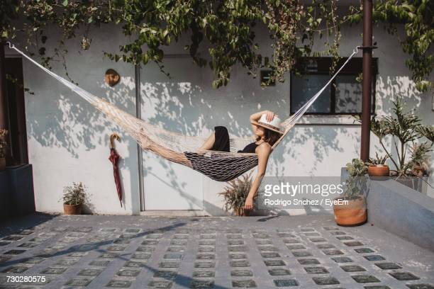 woman relaxing in hammock against wall at yard - pauze nemen stockfoto's en -beelden