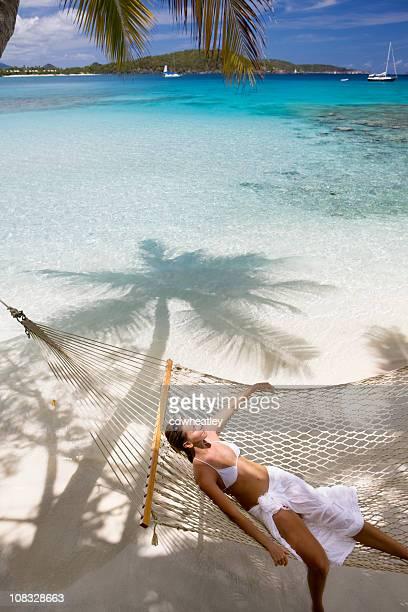 woman relaxing in hammock at the beach - lagune stockfoto's en -beelden
