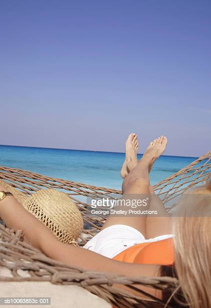 Woman relaxing in hammock on beach, over the shoulder view