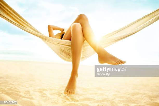 woman relaxing in hammock on beach - leg stock pictures, royalty-free photos & images