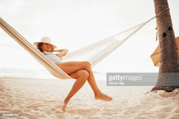 woman relaxing in hammock on beach - serene people stock pictures, royalty-free photos & images