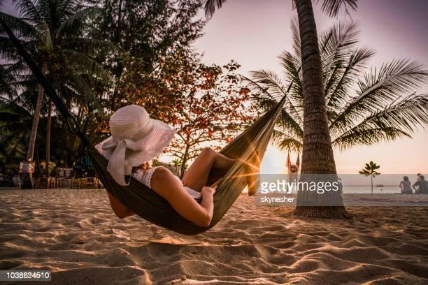 mulher, relaxante em rede na praia ao pôr do sol. - lying down - fotografias e filmes do acervo