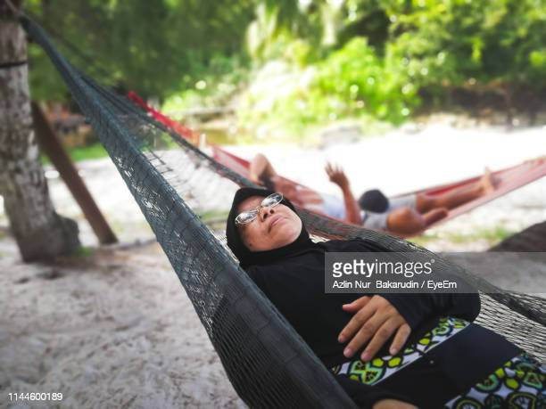 Woman Relaxing In Hammock Over Sand