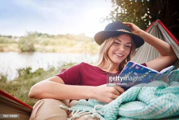 Woman relaxing in hammock reading book, Krakow, Malopolskie, Poland, Europe