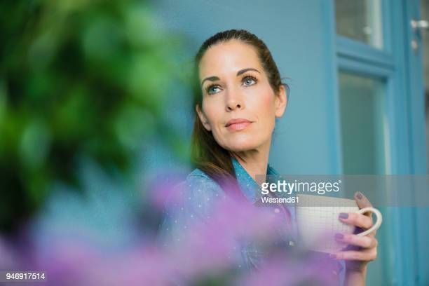 Woman relaxing in her home with potted plants, drinking coffee