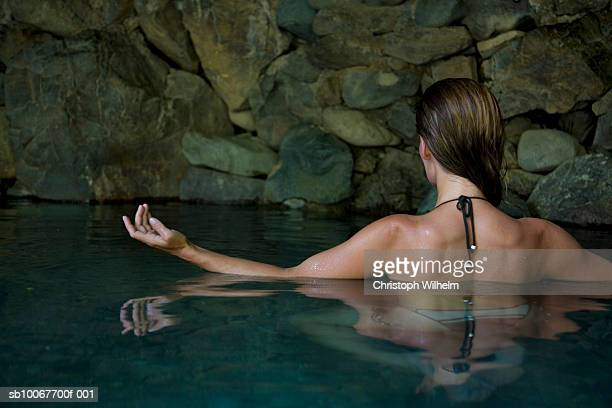 Woman relaxing in hot spring, rear view