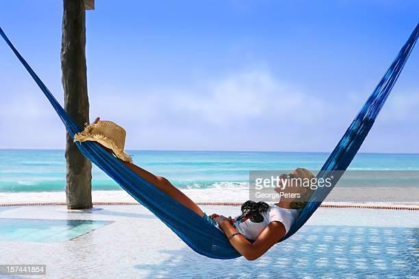 Femme se détendre dans le hamac de la piscine à débordement