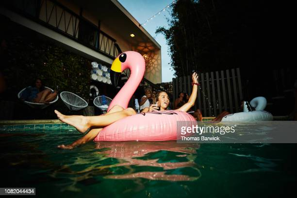 woman relaxing in inflatable flamingo during hotel pool party - swimming float stock pictures, royalty-free photos & images