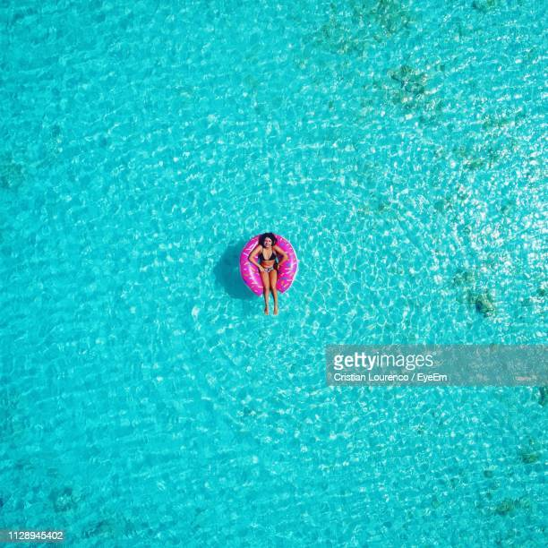 woman relaxing in inflatable ring on swimming pool - inflatable stock pictures, royalty-free photos & images