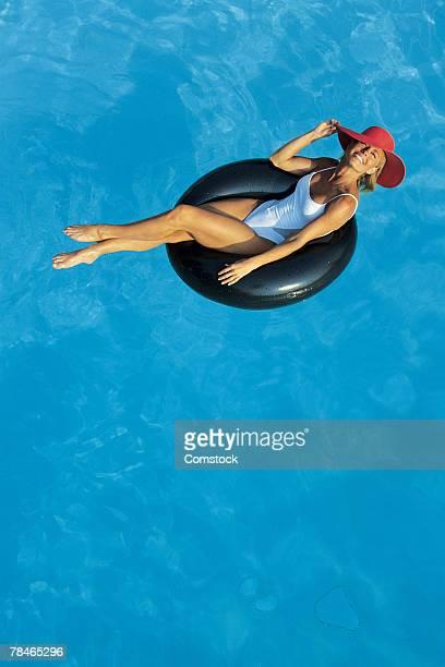 Woman relaxing in inner tube in swimming pool