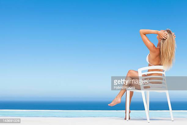 Woman relaxing in lawn chair by pool