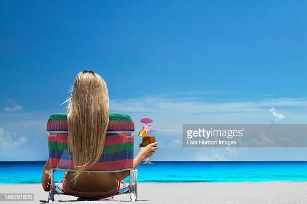 woman relaxing in lawn chair on beach - outdoor chair stock pictures, royalty-free photos & images